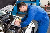 pic of garage  - Mechanic using laptop on car at the repair garage - JPG
