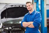 stock photo of garage  - Mechanic smiling at the camera at the repair garage - JPG