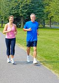 image of mature men  - Happy elderly seniors couple jogging in park - JPG