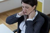 image of spinal column  - Young sitting woman in office with pain of spinal column - JPG