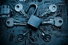 stock photo of spyware  - open security lock on a computer circuit board surrounded by keys  - JPG