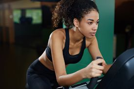 pic of cardio exercise  - Portrait of fit afro american woman exercising on spinning bike at cardio class at gym - JPG