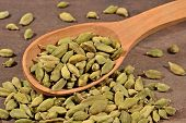 picture of cardamom  - Cardamom seeds in a wooden spoon close up - JPG