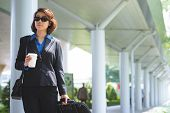 foto of leaving  - Business woman with coffee and luggage leaving the airport - JPG