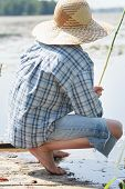 image of rod  - Sitting on wooden bridge barefoot young fisherman with fishing rod - JPG