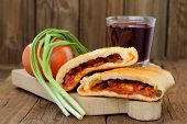 picture of scallion  - Two pieces of pizza calzone with glass of red wine fresh scallion and tomato on wooden board horizontal - JPG