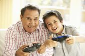 stock photo of grandfather  - Hispanic Grandfather And Grandson Playing Video Game At Home - JPG