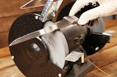 stock photo of knife  - Knife sharpener and hand with blade on wooden table - JPG