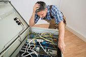 stock photo of electrician  - Portrait Of A Confused Electrician Looking At Fuse Box - JPG