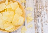 stock photo of potato chips  - Potato chips in wooden plate on white wooden table background - JPG
