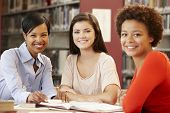stock photo of 16 year old  - 2 Students working in library with teacher - JPG
