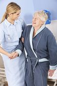 foto of hospital gown  - Nurse helping senior woman out of bed in hospital - JPG