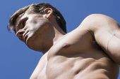 picture of valiant  - Closeup low angle with strong shadows of muscular handsome shirtless Caucasian man with bold facial expression looking forward under bright sunshine and blue sky background - JPG