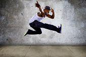 pic of parkour  - Black urban hip hop dancer jumping high on a concrete background - JPG