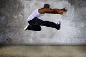 pic of gravity  - Black urban hip hop dancer jumping high on a concrete background - JPG