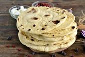 image of pita  - Freshly baked pita bread on a wooden table - JPG