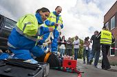 stock photo of ambulance car  - Paramedics tending to the first aid of an injured woman on a stretcher at the scene of a car crash whilst a police woman is escorting a bystander towards the cordon tape being filmed by a camera man - JPG