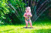 picture of fountain grass  - Child playing with garden sprinkler - JPG