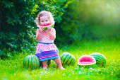 foto of healthy eating girl  - Child eating watermelon in the garden - JPG