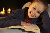 foto of 7-year-old  - Portrait 7 year old girl reading by firelight - JPG