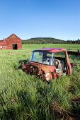 pic of red barn  - The torn up cab of an old truck in the grass near a red barn south of Tensed Idaho - JPG