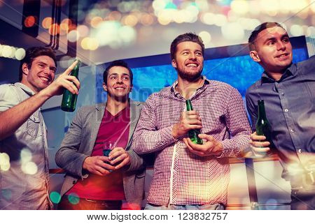 nightlife, party, friendship, leisure and people concept - group of smiling male friends with beer b