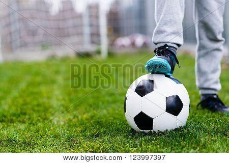 Feet Of Child On Football / Soccer Ball On Grass