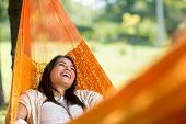 Cheerful girl enjoy in orange hammock outdoor poster