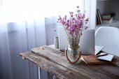 Modern interior. Comfortable workplace. Wooden table with beautiful bouquet of flowers and laptop on poster