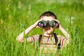 Young boy in a field looking through binoculars