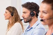 Happy young employees working in call centre. Portrait of a young attractive telephone operator work poster