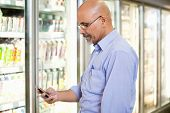 picture of mobile-phone  - Smiling mature man looking at mobile phone while standing in front of refrigerator in supermarket - JPG