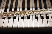 pic of chopin  - A silver flute placed on keys of a piano - JPG