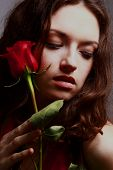 Studio portrait of sensual beautiful woman with rose. poster