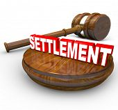 The word Settlement on a wood block beside a judge's gavel, indicating a legal lawsuit has been sett