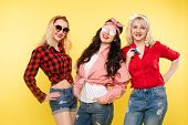 Three Stylish And Trendy Girlfriends.studio Shot Of Trendy Girls With Head Bows, Sunglasses Wearing  poster