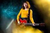 Beautiful Young Hipster Woman With Curly Hair With Red Guitar In Neon Lights. Rock Musician Is Playi poster