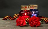 Постер, плакат: Памяти фонарь с свечи красные гвоздики и Георгиевская лента на деревянный стол на сером фоне