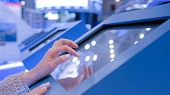 Woman Hand Using Interactive Touchscreen Display Of Electronic Multimedia Terminal At Modern Technol poster