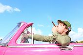 Cuba concept. Vintage car with cigar smoking man with Fidel Castro patrol cap. Funny image cuban con