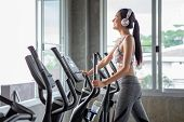 Beautiful Young Asian Woman Exercise On Elliptical Machine And Listening Music With Headphones Relax poster