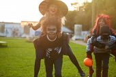 Portrait Of Carefree Kids Playing Outdoors On Halloween And Running Towards Camera Laughing Happily poster