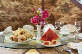 Dishes Of Chinese Food In A Cafe. Served Table In A Cafe Of Chinese Cuisine. A Small Bouquet With Re poster