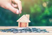 House Placed On Coins. Hand That Is Coin Down The House. Indicates The Growth Of Home And Finance. P poster