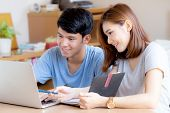 Beautiful Young Asian Couple Calculate Expenses Finance With Laptop And Planning Together, Woman Wri poster