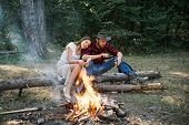 Beautiful Young Couple Enjoying Picnic In A Park. Pleasant Weekend Near Campfire. Couple In Love On  poster
