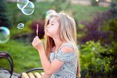 Portrait Of A Beautiful Little Girl, A Child, Sitting On A Bench, In The Park, Blowing Bubbles. Acti poster