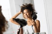 Blow-drying. Smiling African American Woman Drying Hair With Fan Looking In Mirror In Bathroom. Sele poster