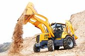 stock photo of backhoe  - Wheel loader Excavator with backhoe unloading sand at eathmoving works in construction site - JPG