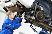 picture of inspection  - car mechanic inspecting car wheel and suspension detail of lifted automobile at repair service station - JPG
